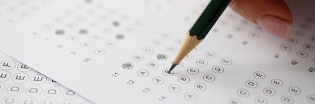 Mulher resolvendo testes e escrevendo a lápis no papel closeup. conceito de teste de exame