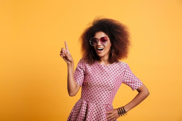 Mulher retrô muito afro americana com penteado afro, apontando com o dedo para cima