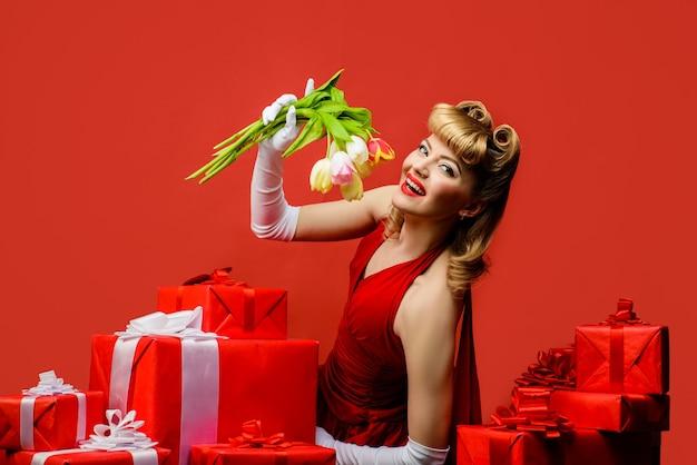 Mulher retro sorridente segurando flores da primavera. linda mulher loira com vestido vermelho e penteado retrô