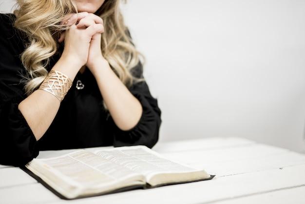 Mulher rezando com os dedos firmemente ligados perto de um livro aberto sobre uma mesa
