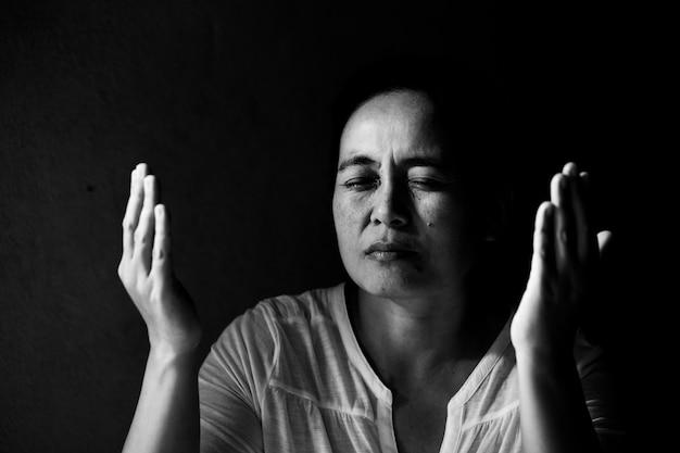 Mulher rezando com os olhos fechados