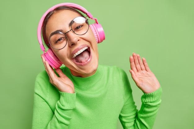 Mulher ri alegremente ouve música favorita em fones de ouvido rosa aprecia faixa de áudio usa óculos redondos transparentes e gola verde