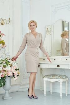 Mulher rica de sucesso sem complexos em poses de peso em casa. jovem pensionista, mulher de negócios