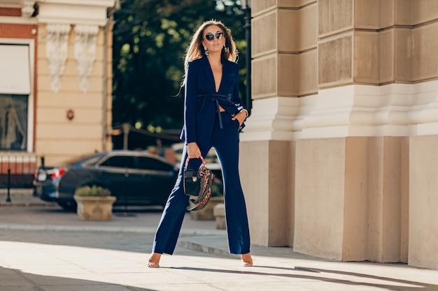 Mulher rica luxuosa vestida com um elegante terno azul elegante caminhando pela cidade em um dia ensolarado de outono segurando uma bolsa