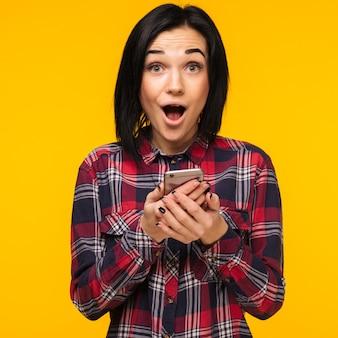 Mulher rindo animada com uma camisa xadrez em pé e usando o telefone celular sobre fundo amarelo