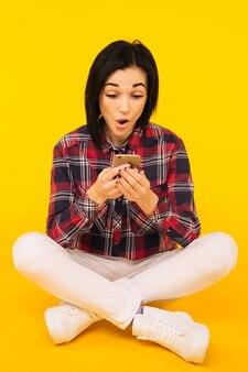Mulher rindo animada em uma camisa xadrez sentada e usando o telefone celular sobre fundo amarelo - imagem