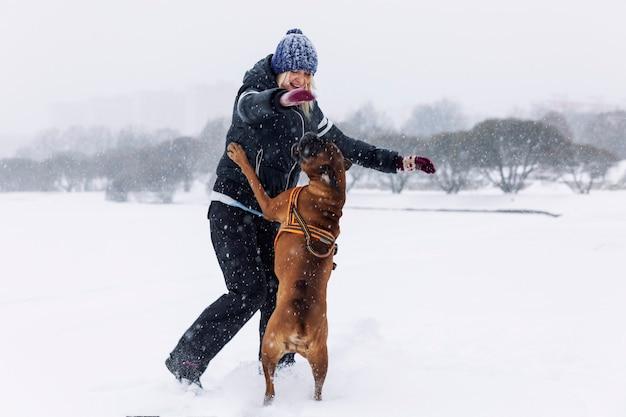 Mulher rindo brinca com cão boxer em winter park. amor e amizade.