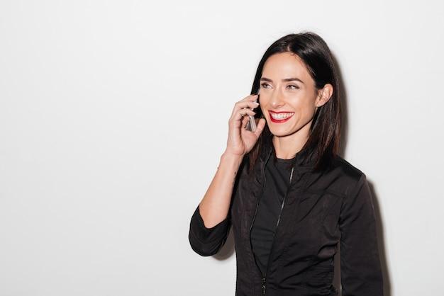 Mulher rindo com lábios vermelhos, falando pelo telefone móvel.