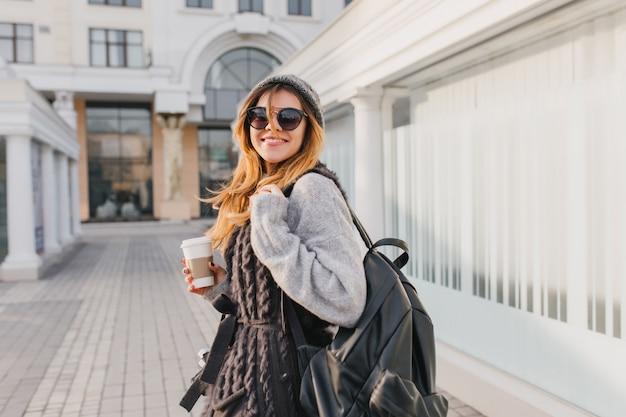 Mulher rindo com mochila preta, andando pela cidade e bebendo café em um bom dia. retrato ao ar livre da mulher viajante sorridente com camisola e chapéu posando