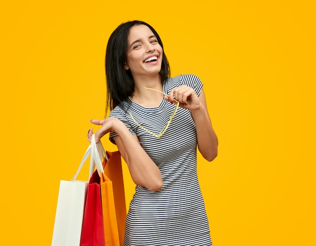 Mulher rindo com sacos de papel