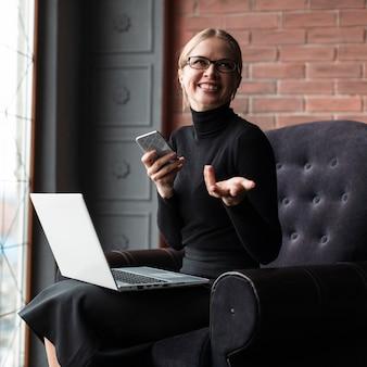 Mulher rindo com telefone e computador portátil