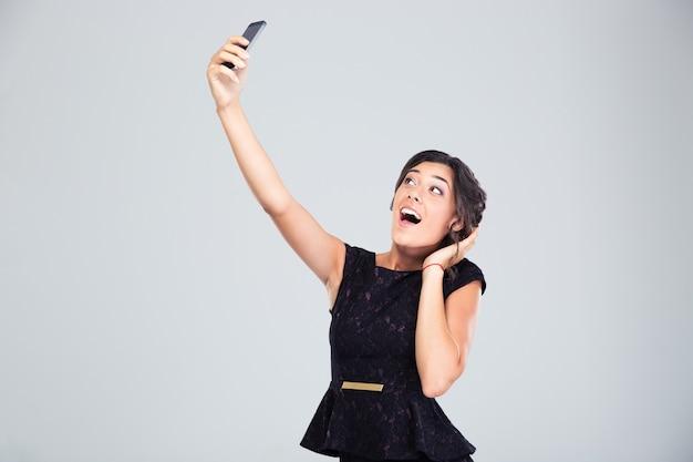 Mulher rindo de vestido preto fazendo selfie foto
