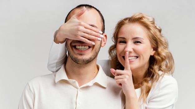 Mulher rindo e cobrindo os olhos do homem