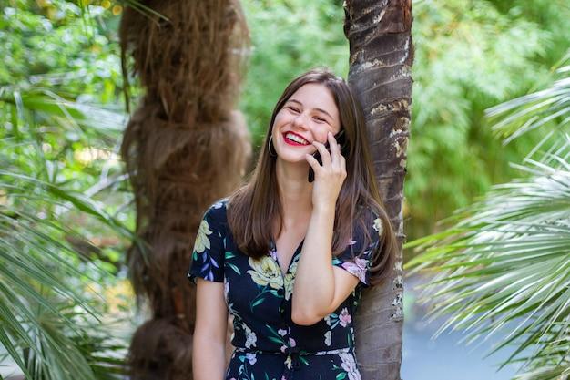 Mulher rindo e falando em smartphone no parque