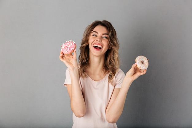 Mulher rindo em t-shirt mostrando donuts e mais cinza