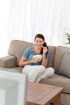 Mulher rindo enquanto assistia a um filme na televisão na sala de estar