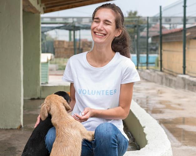 Mulher rindo enquanto brinca com cães de resgate no abrigo