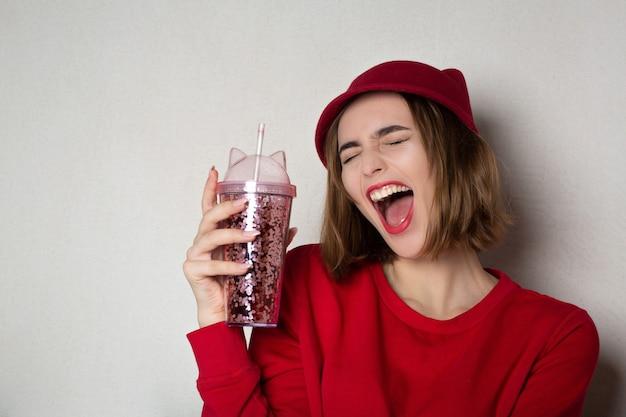 Mulher rindo feliz no suéter vermelho e boné segurando o copo de suco de cereja. espaço para texto