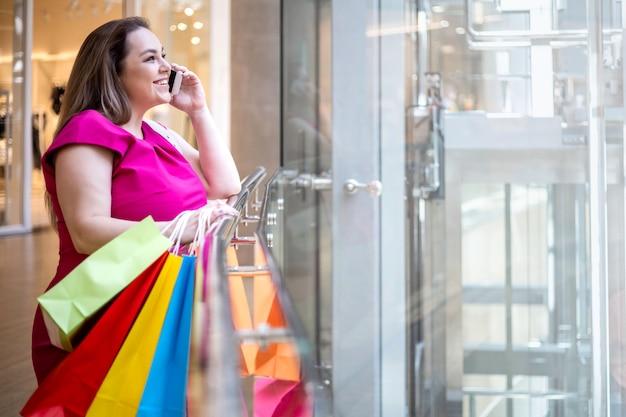 Mulher rindo glamour plus size falando smartphone com sacola de papel em um shopping moderno