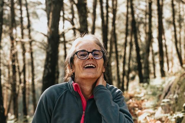 Mulher rindo no meio da floresta durante um dia ensolarado de outono