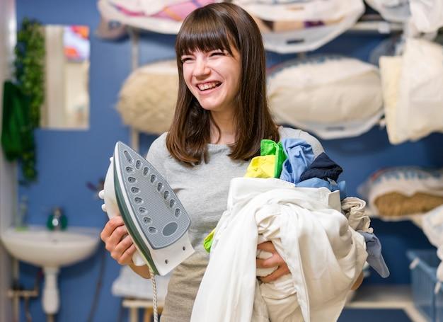 Mulher rindo segurando a roupa limpa