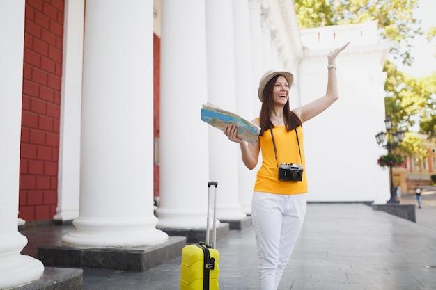 Mulher rindo viajante turista com mala, cidade mapa retrô vintage foto câmera reunião amigo, espalhando as mãos na cidade ao ar livre. garota viajando para o exterior em uma escapadela de fim de semana. estilo de vida da viagem de turismo.