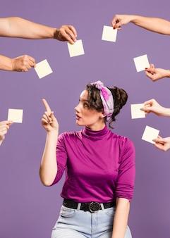 Mulher rodeada de mãos e notas autoadesivas, escolhendo uma nota vazia
