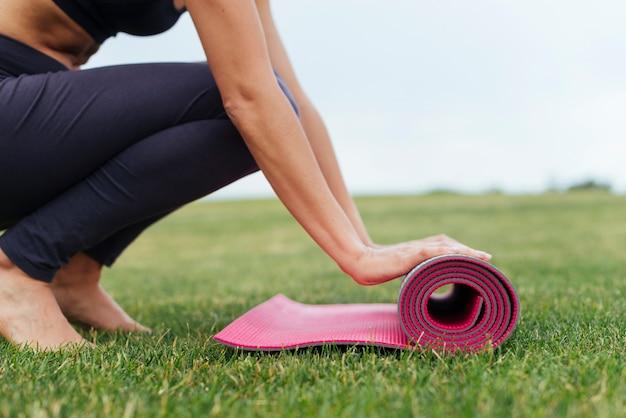 Mulher, rolando, esteira yoga, ao ar livre