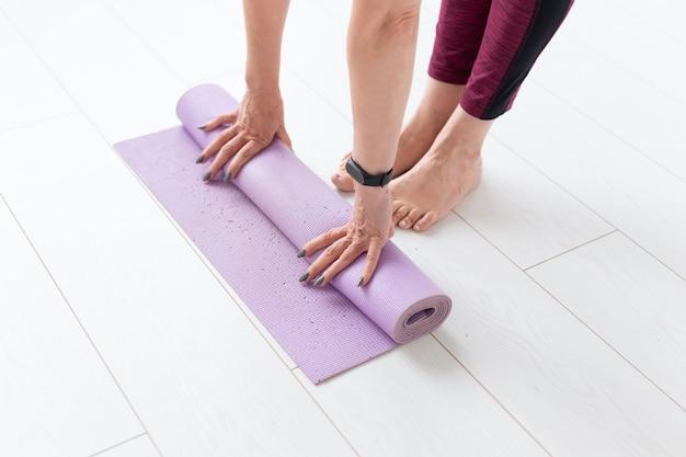 Mulher rolando o tapete depois de uma aula de ioga
