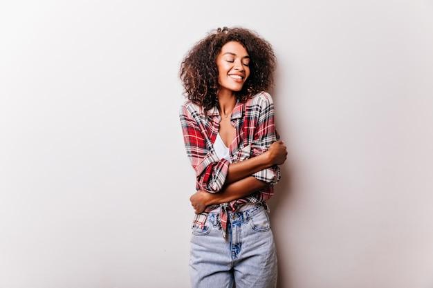 Mulher romântica africana sorrindo com os olhos fechados. fascinante garota negra em camisa quadriculada vermelha, posando com uma expressão de rosto sonhadora.