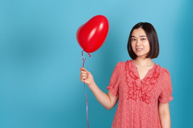 Mulher romântica asiática com vestido vermelho e cabelo escuro segurando um balão voador em forma de coração vermelho
