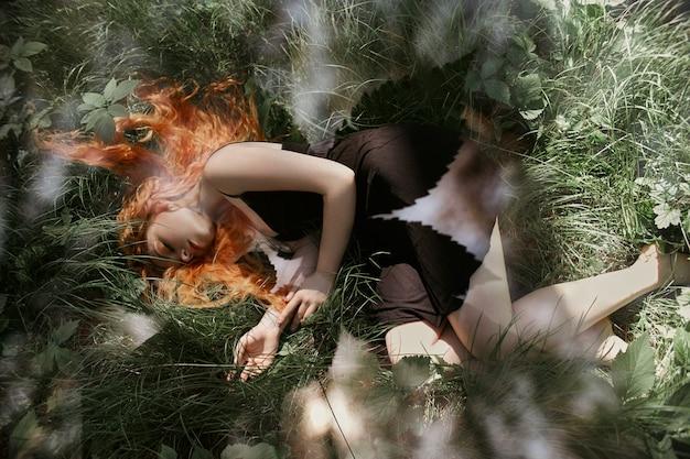 Mulher romântica com cabelo vermelho, deitado na grama