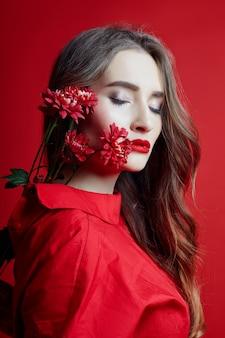 Mulher romântica, com longos cabelos loiros e flores nas mãos em um vestido vermelho, pele limpa e macia