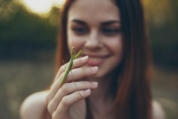 Mulher romântica com louva-a-deus na mão ao ar livre no prado.