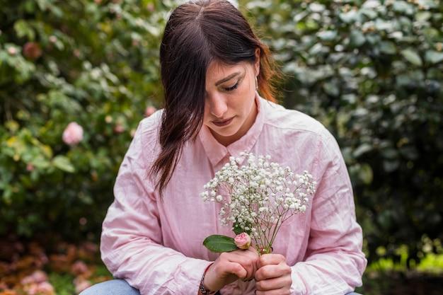 Mulher romântica com monte de flores no parque