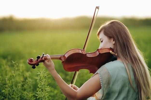 Mulher romântica com o cabelo solto tocando violino ao ar livre na grama verde