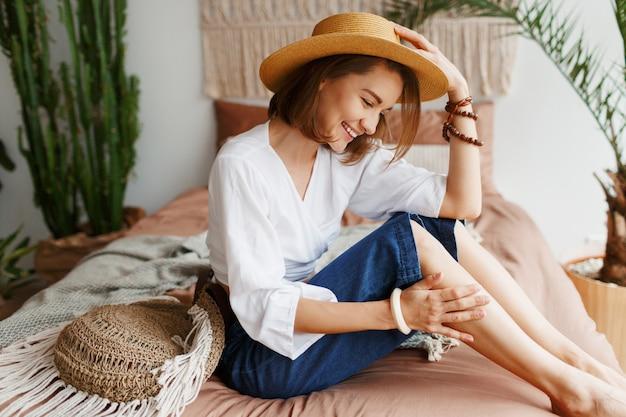 Mulher romântica com sorriso sincero, sentado na cama, aproveitando a manhã ensolarada em seu apartamento elegante no estilo boho