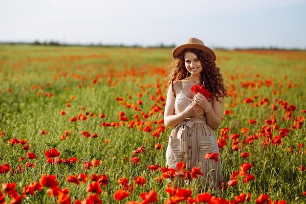 Mulher romântica com uma flor na mão ficando em um campo de papoulas