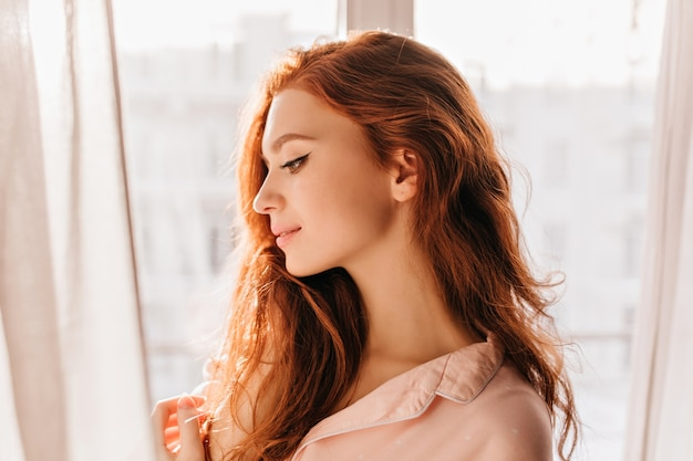 Mulher romântica de cabelos compridos, posando em casa. retrato de menina ruiva atraente pensativa.