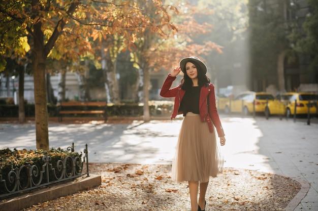 Mulher romântica de cabelos negros com saia longa exuberante aproveitando o sol no parque outono