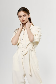 Mulher romântica em roupas leves, toca o rosto com as mãos no fundo isolado.