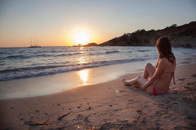 Mulher romântica em um pôr do sol em ibiza, olhando para o ver