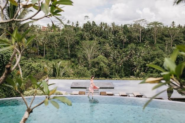 Mulher romântica em um vestido longo, desfrutando de descanso no resort exótico. retrato ao ar livre do modelo feminino se passando perto da floresta em dia chuvoso.