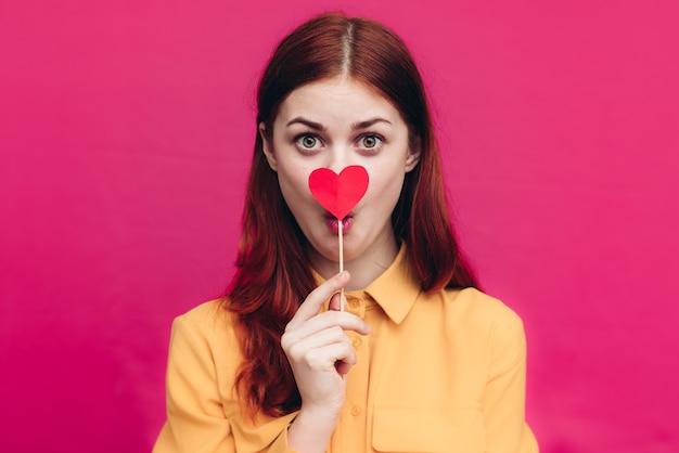 Mulher romântica em uma camisa com corações em um palito na parede rosa