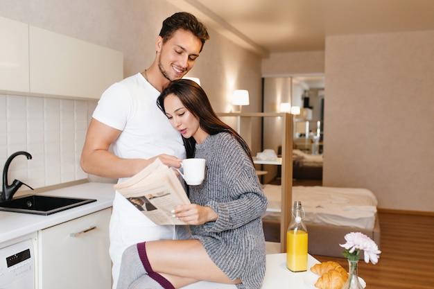 Mulher romântica em vestido de malha lendo jornal e abraçando o marido