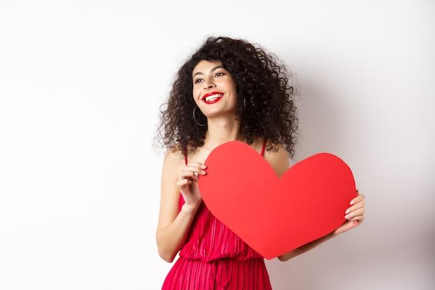 Mulher romântica em vestido e maquiagem, olhando de lado com rosto sonhador e amor, mostrando um grande cartão de coração vermelho de dia dos namorados, de pé sobre fundo branco.
