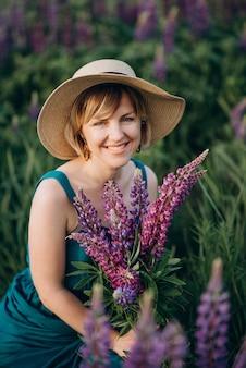 Mulher romântica feliz sorrindo em um vestido azul e chapéu em um campo com um buquê de flores roxas de tremoço.
