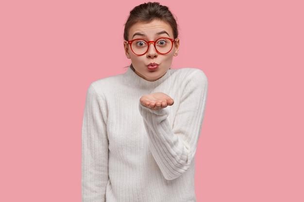 Mulher romântica feminina tem expressão fofa, dá mwah, manda beijo no ar para você, compartilha seu amor, usa óculos ópticos, suéter branco de gola alta