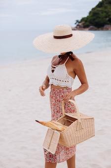Mulher romântica na praia com saia de malha e chapéu de palha segurando uma cesta com pão vida ecológica