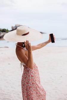 Mulher romântica na praia com saia de malha e chapéu de palha